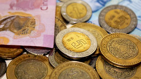 Mexican coins and bills. Five, one and ten pesos coins and some bills stock image