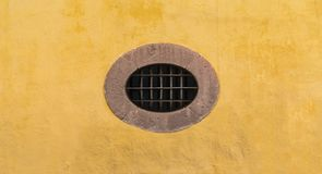 Mexican colonial oval peculiar window with yellow wall royalty free stock photo