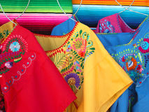 Mexican colorful dresses. Mexican traditional market dresses and sarapes Royalty Free Stock Photos