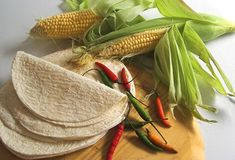 Mexican cooking ingredients. Corn,tortillas and chilies on a cutting board stock images