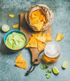 Mexican corn chips, fresh guacamole sauce and beer, concrete background Stock Photos