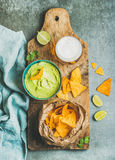 Mexican corn chips, fresh guacamole sauce and beer, top view Stock Photos