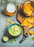 Mexican corn chips, fresh guacamole sauce and glass of beer Stock Photos