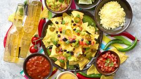 Mexican corn nacho spicy chips served with melted cheese. Peppers, tomatoes, beer and side salsas stock footage
