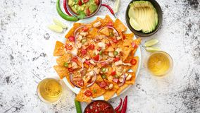 Mexican corn nacho spicy chips served with melted cheese. Peppers, tomatoes, beer and side salsas stock video footage