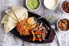Mexican cuisine fajitas. Portrait of mexican cuisine fajitas served with soft flour tortillas, rice, bean chili, salsa, guacamole and sour cream Royalty Free Stock Images