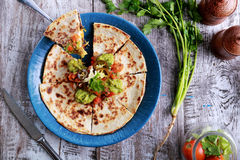 Mexican cuisine quesadilla. Top view mexican cuisine quesadilla served at blue plate with guacamole, salsa and jalapenos royalty free stock photo