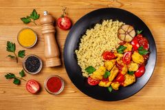 Mexican cuisine. Rice with black sesame. Spicy chicken with curry, paprika, cherry tomatoes and honest. Red Salsa Sauce Serve. In a black plate, near spices royalty free stock images