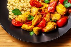 Mexican cuisine. Rice with black sesame. Spicy chicken with curry, paprika, cherry tomatoes and honest. Red Salsa Sauce Serve. In a black plate, near spices royalty free stock image