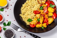 Mexican cuisine. Rice with black sesame. Spicy chicken with curry, paprika, cherry tomatoes and honest. Red Salsa Sauce Serve. In a black plate, near spices royalty free stock photos