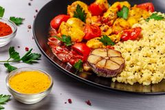 Mexican cuisine. Rice with black sesame. Spicy chicken with curry, paprika, cherry tomatoes and honest. Red Salsa Sauce Serve. In a black plate, near spices stock images