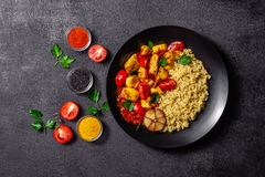 Mexican cuisine. Rice with black sesame. Spicy chicken with curry, paprika, cherry tomatoes and honest. Red Salsa Sauce Serve. In a black plate, near spices royalty free stock photography