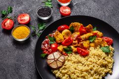 Mexican cuisine. Rice with black sesame. Spicy chicken with curry, paprika, cherry tomatoes and honest. Red Salsa Sauce Serve. In a black plate, near spices stock photo