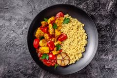 Mexican cuisine. Rice with black sesame. Spicy chicken with curry, paprika, cherry tomatoes and honest. Red Salsa Sauce Serve. In a black plate, near spices stock photos