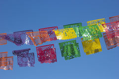 Mexican decorative Papers. Mexican typical decorative papers called Papel picado with the word Tropical set over a street over a blue and clear sky Stock Photo
