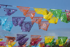 Mexican decorative Papers. Mexican typical decorative papers called Papel picado with the word Tropical set over a street over a blue and clear sky Stock Photos