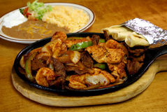 Mexican Deluxe Supreme Fajitas. Grilled and seasoned chicken breast, steak strips and shrimp fajitas with grilled onions and green bell peppers.  Shown served Royalty Free Stock Image