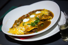 Mexican dish enchillada stuffed with hot meat. Mexican enchilada corn tortilla covered chili pepper sauce in plate Stock Photo
