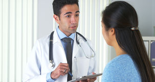 Mexican doctor listening to patient and taking notes Royalty Free Stock Photo