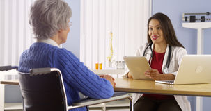 Mexican doctor talking with elderly patient Stock Images