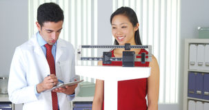 Mexican doctor weighing Chinese patient Royalty Free Stock Images