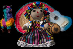 Mexican Doll and Toys. Mexican doll, pinata, guitar, hat, and maracas isolated on black background Stock Photography