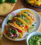 Mexican fajita tacos in yellow corn tortilla served with guacamole stock image
