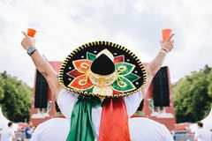 Mexican fans in uniform and sombrero are happy for their team during the World Cup. Horizontal stock image
