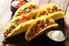 Mexican fast food tacos with chopped beef, cheese and vegetables served with sauces close-up on a slate boarde. horizontal stock images
