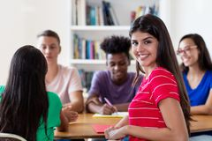Mexican female student learning with group of students stock images