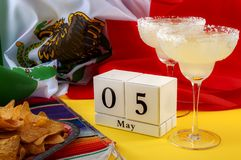 Mexican fiesta and Cinco de Mayo party concept theme with block calendar set on May 5th, traditional rug or serape, two margaritas. Bowl of tortilla chips and stock photo