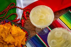 Mexican fiesta and Cinco de Mayo party concept theme with jalapeno pepper beads necklace, traditional rug or serape, two margarita. Glasses, chips and the flag stock image