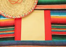 Mexican fiesta frame poncho sombrero. Traditional Mexican fiesta poncho rug in bright colours background with copy space and sombrero Stock Image