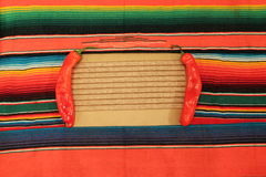 Mexican fiesta poncho rug and chillis in bright co. Traditional Mexican fiesta poncho rug frame in bright colours background with copy space and chilli red
