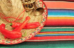 Mexican fiesta poncho background sombrero chilli mariachi. Mexican fiesta poncho frame chilli sombrero background with copy space and trumpet mariachi Stock Photo