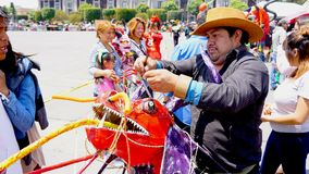 Mexican fireworks man. An adult man prepares a hand crafted paper demon, man wearing a hat ties some parts of a dragon demon sculpture, mexican traditional Judas Stock Photos