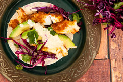 Mexican fish tacos. Fresh, home made fish tacos served with avocado and a red cabbage side salad. Presented on a rustic wooden table Stock Photography
