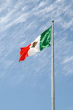 Mexican Flag. Against a cloudy blue sky Royalty Free Stock Photography
