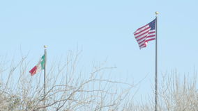 Mexican Flag with the American Flag. The Mexican flag and the American flag fly high together in the wind stock video footage