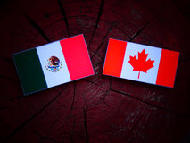 Mexican flag with Canadian flag on a tree stump isolated Royalty Free Stock Photo