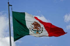 Mexican Flag. Horizontal shot of the mexican flag being moved by the wind over sky and clouds on a sunny day Royalty Free Stock Photography