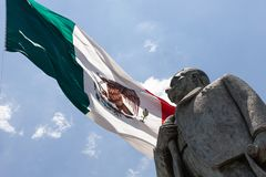 Statue of Manuel Jose other with the Mexican flag in background. Mexican flag with Statue of Manuel Jose Othon royalty free stock image
