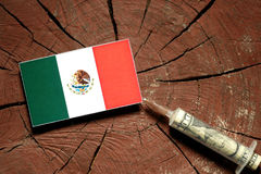 Mexican flag on a stump with syringe injecting money. In flag Stock Photos