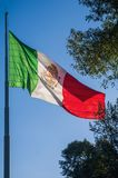 Flag of Mexico waving on a flagpole. A Mexican flag waves majestically on top of a flagpole located in the Luis G. Urbina Park, popularly known as the Sunken royalty free stock images