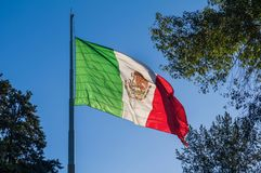 Flag of Mexico waving on a flagpole. A Mexican flag waves majestically on top of a flagpole located in the Luis G. Urbina Park, popularly known as the Sunken stock photography