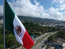Mexican Flag waving on Acapulco Bay, Mexico, Aerial View Stock Photo