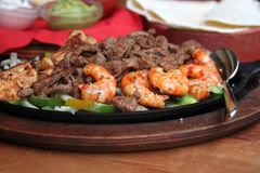 Mexican food. Traditional Mexican fajitas grilled served on a frying pan Stock Image