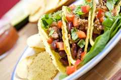 Mexican food. Tacos stuffed with beans meat salad and tomatoes Stock Image