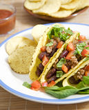 Mexican food. Tacos stuffed with beans meat salad and tomatoes Stock Images