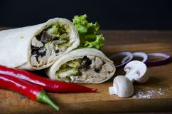 Mexican Food Burrito with chicken, mushrooms, salad and sauces with a red chili peppers and cut mushrooms onion on. Wooden platform with blue paper background Royalty Free Stock Image